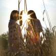 Two girls standing  at sunset - Stock Photo