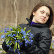 Stock Photo: A girl young women with bunch of bluebells in spring forest