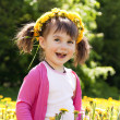 A smiling girl sitting on the dandelion field with the dandelion — Stock Photo