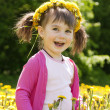 A smiling girl sitting on the dandelion field with the dandelion — Stock Photo #9677029