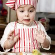 Little chef in the kitchen ,wearing an apron and headscarf,surpr - Stock Photo