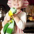 Little chef in the kitchen wearing an apron and headscarf - Stock Photo