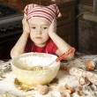 Little chef in the kitchen wearing an apron and headscarf — Stock Photo #9703934