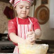 Little chef in the kitchen wearing an apron and headscarf — Foto Stock