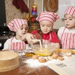 Three little chefs enjoying in the kitchen making big mess. Litt - Stock Photo