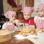 Three little chefs enjoying in the kitchen making big mess. Litt — Stock Photo