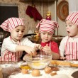 Stock Photo: Three little chefs enjoying in the kitchen making big mess. Litt