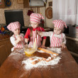 Three little chefs enjoying in the kitchen making big mess. Litt — Stock Photo #9703990