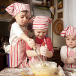 Three little chefs enjoying in the kitchen making big mess. Litt — Stock Photo #9703997