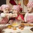 Stock Photo: Three little chefs enjoying in kitchen making big mess. Litt
