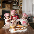 Three little chefs enjoying in the kitchen making big mess. Litt — ストック写真