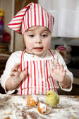 Little chef in the kitchen ,wearing an apron and headscarf,surpr — Stock Photo