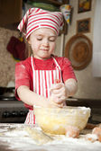 Little chef in the kitchen wearing an apron and headscarf — Stock Photo