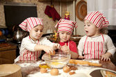 Three little chefs enjoying in the kitchen making big mess. Litt — Stock Photo