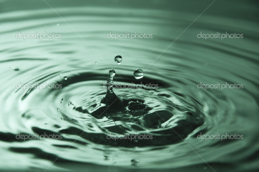 Water drops splashing into a puddle and making ripples — Stock Photo #9467125