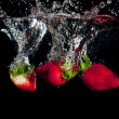 Strawberries Splashing Into Water — Stock Photo