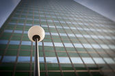 Lamp post in front office building facade — Stock Photo