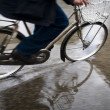 Man on bicycle in puddle - Stock Photo