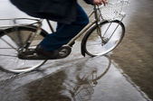Man on bicycle in puddle — Stock Photo