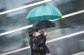 Two women under umbrella in rain — Stock Photo