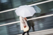 Woman under umbrella in rain — Stock Photo