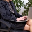Business woman sitting and working with notebook on her knees — Stock Photo