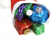 Many colorful christmas gifts in a santa claus cap on white background — Stock Photo #10487639