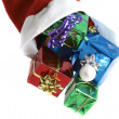 Many colorful christmas gifts in a santa claus cap on white background — Stock Photo #10487643