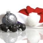 Santa claus cap and christmas balls mirrored on white background — Stock Photo