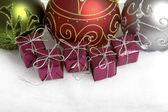 Três enfeites de natal e alguns pacotes de pequeno presente em fundo branco — Foto Stock