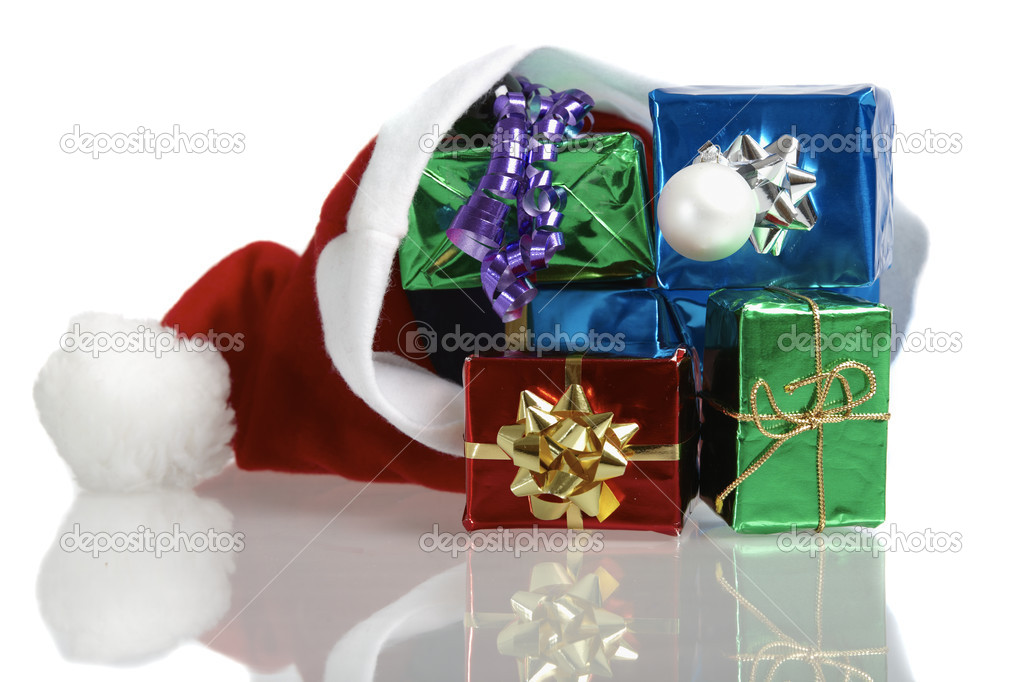 Many colorful christmas gifts in a santa claus cap on white background — Stock Photo #10487654