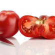 Two large organic tomatoes, one whole and one half mirrored in front of white background — Stock Photo #9599660