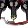 Corkscrew opened in front of a three wine bottle - Stock Photo