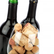 Stock Photo: Wine glass filled with corks are standing in front of two wine bottles