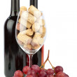 Wine glass filled with corks are standing in front of two wine bottles and grapes — Stock Photo #9601382