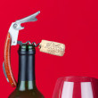 A corkscrew with cork on the top of bottleneck beside of a glass of red wine — Stock Photo #9601441