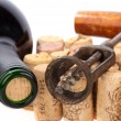 Older corkscrew lies on some corks beside wine bottle — Stock Photo #9601528