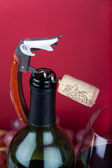 A corkscrew with cork on the top of bottleneck beside of a glass of red wine — 图库照片