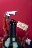 Un tire-bouchon avec bouchon en liège sur le dessus du goulot d'étranglement à côté d'un verre de vin rouge — Photo