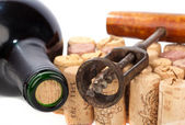 Older corkscrew lies on some corks beside a wine bottle — Stock Photo