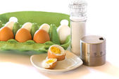 Chicken eggs and egg cups, eggtimer and salt mill — Stock Photo