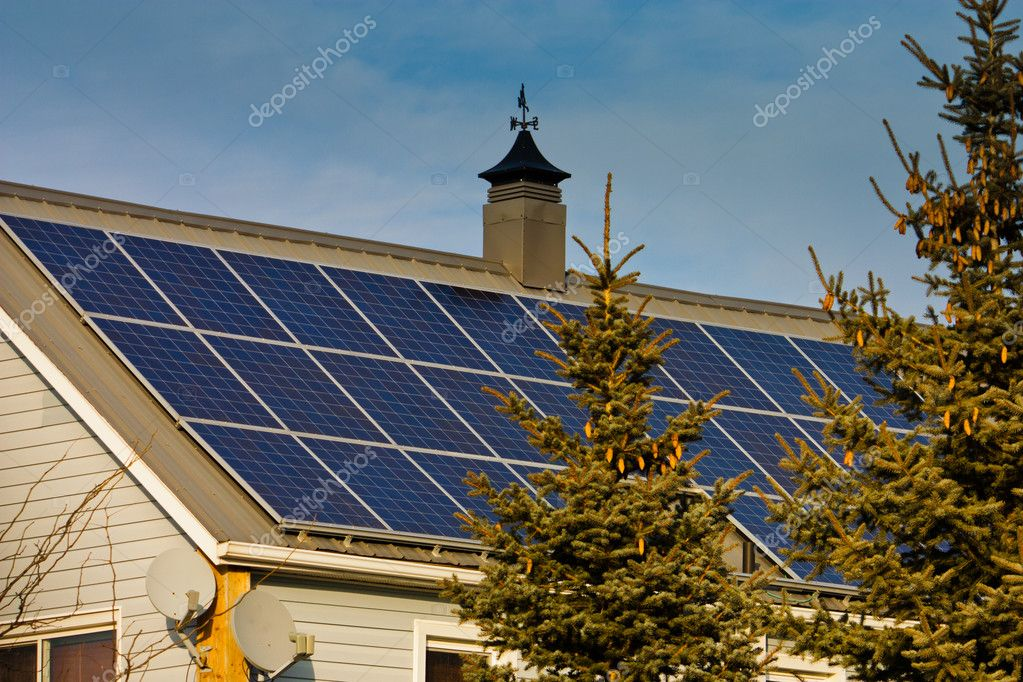 The rooftop of a residential home is shown, filled with solar panels. — Stock Photo #10043305