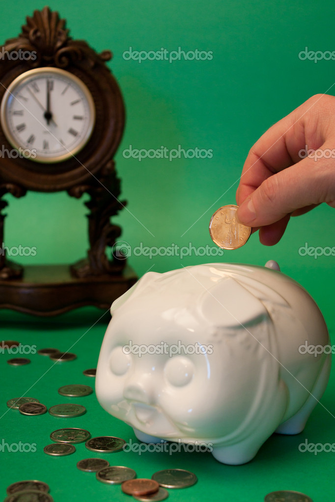 Coins are scattered around a white piggy bank, with a hand dropping a coin in, as a clock in the background approaches 12  Stock Photo #9827313