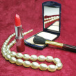 Foto Stock: Red lipstick powder and beads