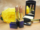 Two brown lipsticks powder and yellow rose — Stock Photo