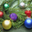 Photo: Christmas balls among fir branches with candle