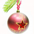 Red christmas ball hanging on fir branch — Stock Photo