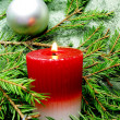Foto Stock: Red candle and christmas among fir branches