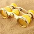 Binoculars on sand — Stockfoto