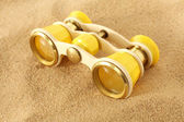 Binoculars on sand — Stock Photo